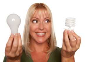 Woman Holds Energy Saving and Regular Light Bulbs Isolated on a White Background.